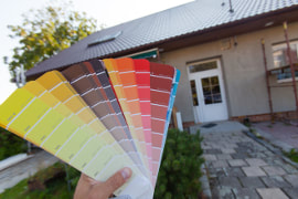 Point of view image of house exterior with person holding color swatches in the foreground