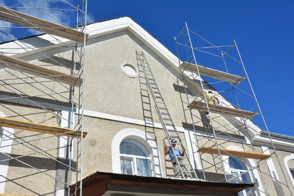 Exterior of home being painted with professional painters, ladders and scaffolding