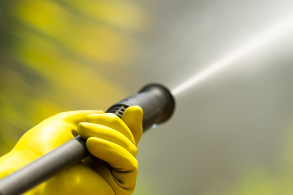 Close up image of pressure washer spray in gloved hand