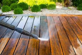 A wood deck being pressure washed showing the progress made by the cleaning process